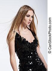 Beautiful blond fashionable girl in black dress