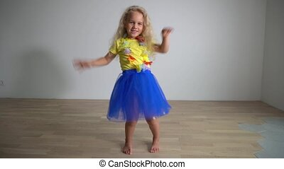 Beautiful blond girl child dance in front of camera. Gimbal...