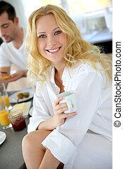 Beautiful blond girl drinking coffee for breakfast