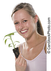 Beautiful blond girl holding young plant
