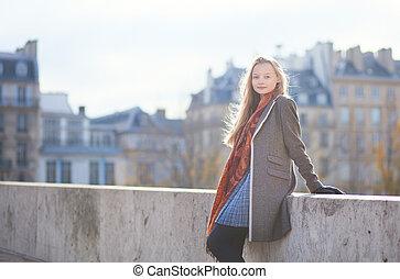 Beautiful blond girl in Paris on a bridge