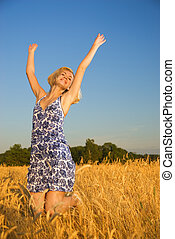 Beautiful blond girl jumping in the wheat field