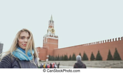 Beautiful blond girl posing against a red square in Moscow. Russia.