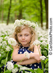 beautiful blond girl sitting in white meadow
