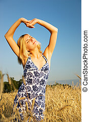 Beautiful blond girl stretching in the wheat field