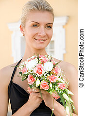 Beautiful blond girl with a bouquet of roses
