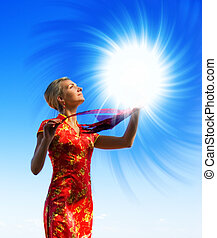 Beautiful blond girl with a magic light sphere over crystal...
