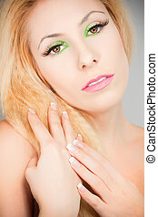 Beautiful blond girl with cat eyes make-up in green