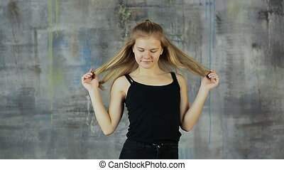 Beautiful blond hair teen girl dancing hiphop on the gray wall. Actively works with hands.