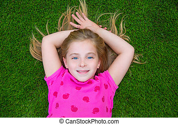Beautiful blond kid children girl smiling lying on grass