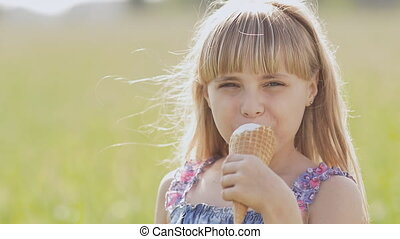 Beautiful blond little girl eats ice-cream in the summer against the background of a wheat field. Warm sunny day.