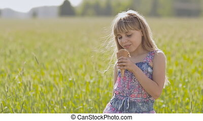Beautiful blond little girl eats ice-cream in the summer next to the wheat field. Warm sunny day.