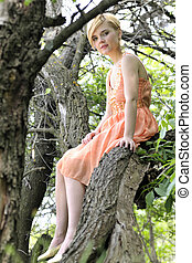 Beautiful blond lying on tree
