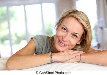 Beautiful blond mature woman relaxing in sofa