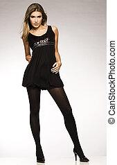 beautiful blond model in black dress posing on grey background