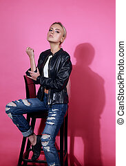 Beautiful blond model posing in black leather jacket and blue ripped jeans on chair on pink background. Fashion portrait