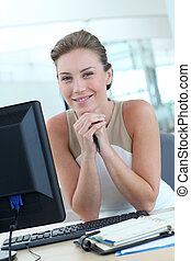 Beautiful blond office-worker sitting at her desk