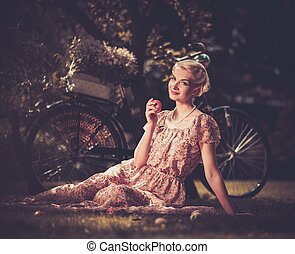 Beautiful blond retro woman with an apple and bicycle behind her