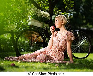 Beautiful blond retro woman with an apple and bicycle behind...