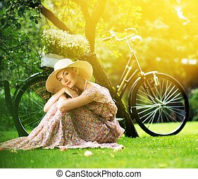 Beautiful blond retro woman with bicycle behind her