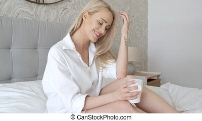 Beautiful blond woman drinking a coffee while sitting on her...