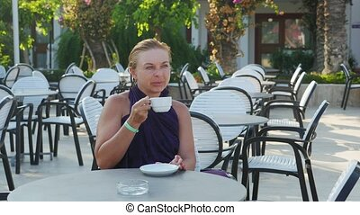 Beautiful blond woman drinking a cup of coffee in a modern cafe in slo-mo