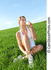 Beautiful blond woman drinking milk in countryside