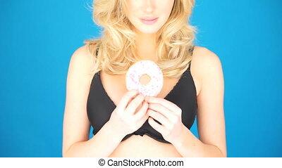 Beautiful blond woman eating a big doughnut