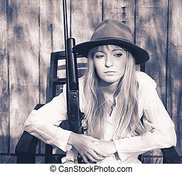 Beautiful blond woman holding rifle sitting in front of a wooden wall