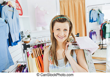 Beautiful blond woman holding shopping bags smiling at the camera in a clothes store