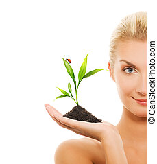 Beautiful blond woman holding young plant