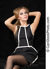 beautiful blond woman in a black dress on a dark background,