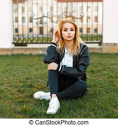 Beautiful blond woman in a black jacket and black jeans with white shoes resting on the grass