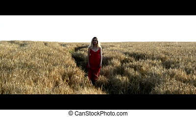 Beautiful blond woman in a red dress, walking on a wheat field at sunset