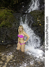 blond woman in a waterfall