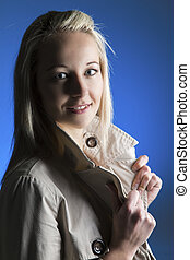 Beautiful blond woman in beige jacket in dark with selective lighting and blue background