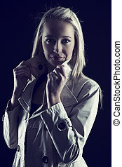 Beautiful blond woman in beige jacket in dark with selective lighting artistic conversion