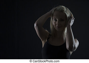 Beautiful blond woman in black top in dark with selective lighting and hands in hair