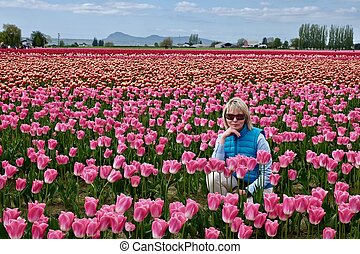 Beautiful blond woman in colorful tulip fields.