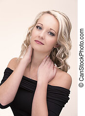 Beautiful blond woman in curly hair and black top on light background