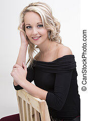 Beautiful blond woman in curly hair and black top sitting on wood chair