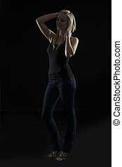 Beautiful blond woman in denim and black top in the dark with selective lighting