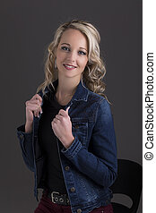 Beautiful blond woman in denim jacket and black top in dark with selective lighting