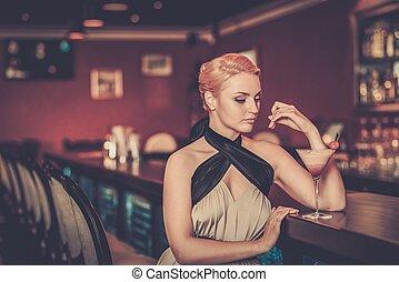 Beautiful blond woman in evening dress sitting near bar...