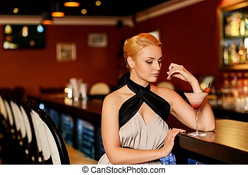 Beautiful blond woman in evening dress sitting near bar counter