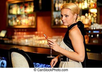 Beautiful blond woman in evening dress standing near bar counter
