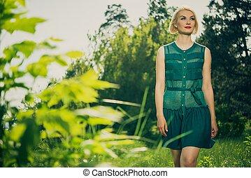 Beautiful blond woman in green dress outdoors