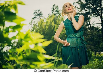Beautiful blond woman in green dress outdoors