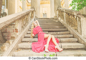 Beautiful blond woman in long dress outdoors
