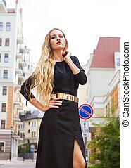 Beautiful blond woman in long dress walking outdoors